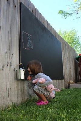 paint chalk board on backyard fence for outdoor kids play area