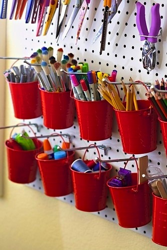 red bucket containers hanging from pegboard for activity room storage