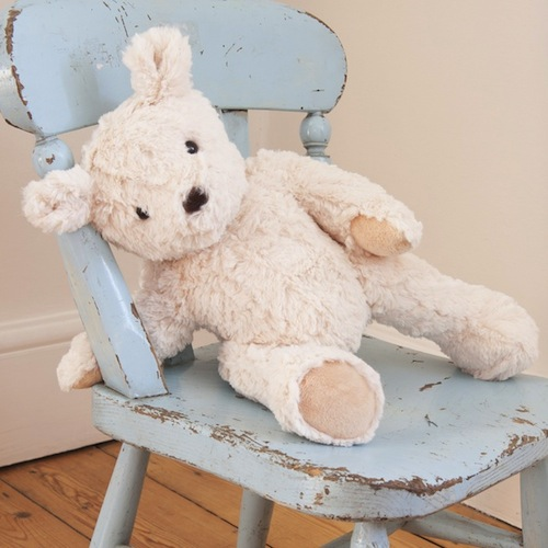 stuffed bear sitting on child's vintage chair