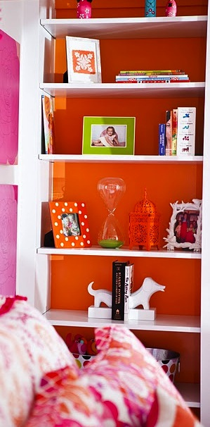 orange wall behind bookcase shelves